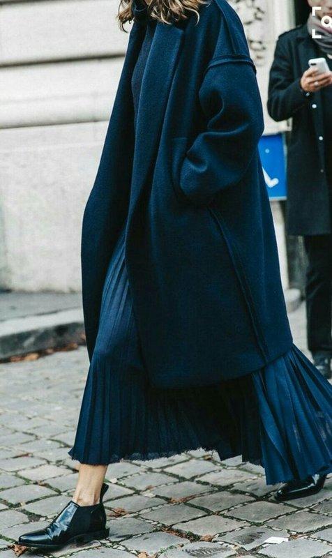 Lange oversized jas gecombineerd met een geplooide lange rok
