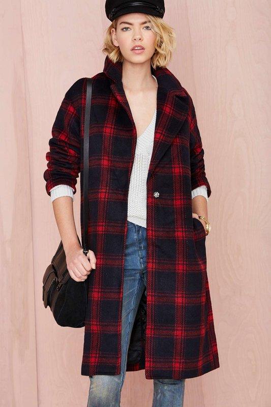 Meisje in een jas in een grote kooi