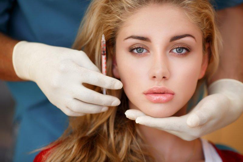 Het meisje bij de afspraak van de schoonheidsspecialiste voor de correctie van permanente lipmake-up