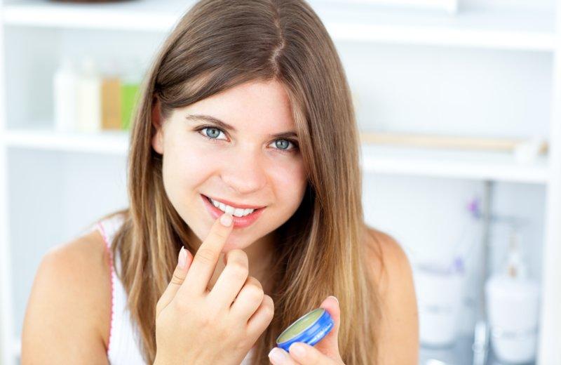 Meisje smeert haar lippen met vaseline