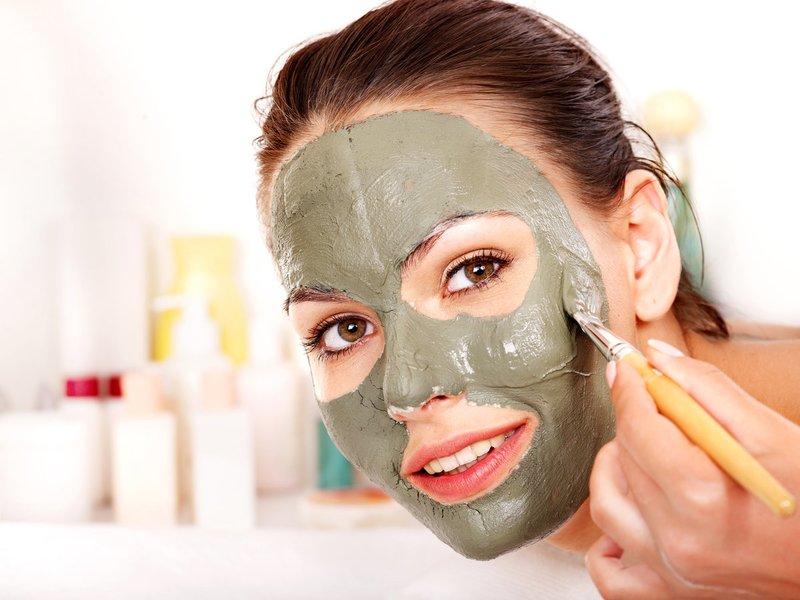 Het meisje zet klei reinigend masker op haar gezicht