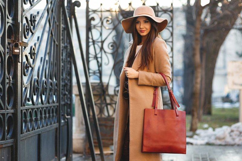 Stilinga mergina smėlio spalvos skrybėlėje