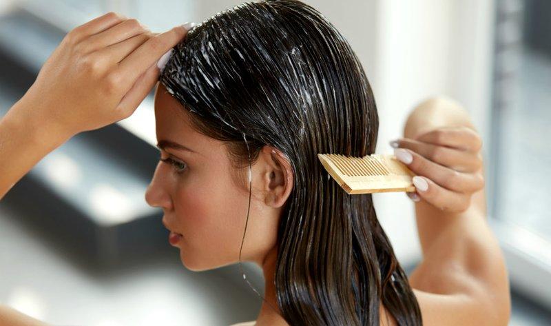 Meisje zet een masker op haar haar met een kam