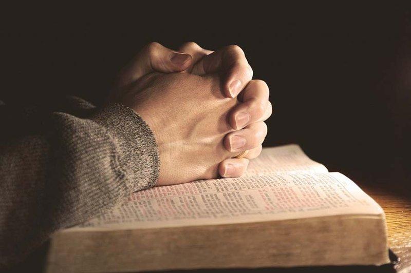 Biddende handen op Bijbel