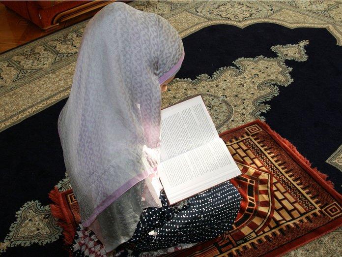 Moslimvrouw die voor huis het schoonmaken bidt