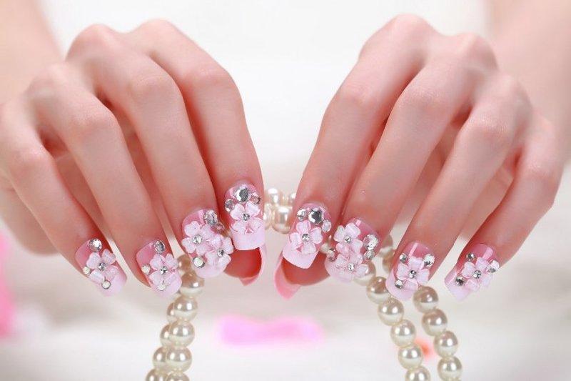 Felroze manicure met acrylbloemen en strass steentjes.