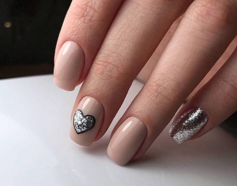 Ongebruikelijke naaktmanicure met glitter en een zilveren hart.