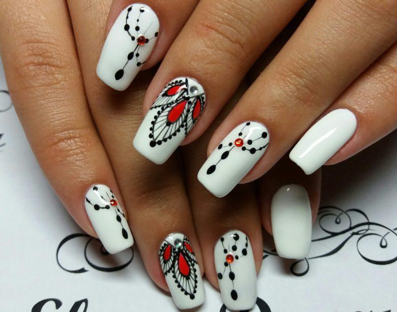 Ongles blancs à motifs noirs et rouges
