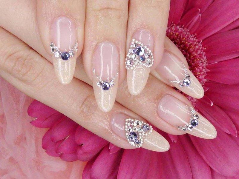 Naakte manicure met veelkleurige steentjes en hart.