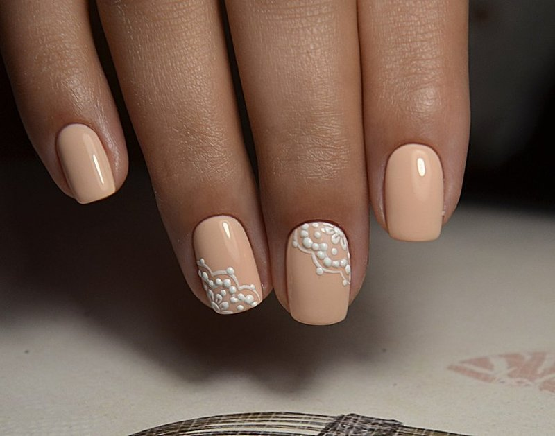 Oranje-beige manicure met wit kant.