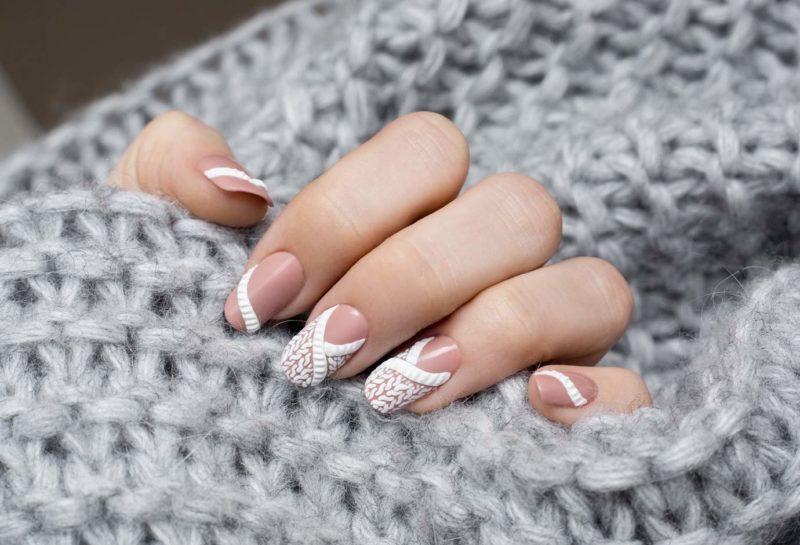 Modèle tricoté blanc sur des ongles de longueur moyenne
