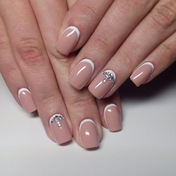 Naakt manicure met witte gaten en strass steentjes.