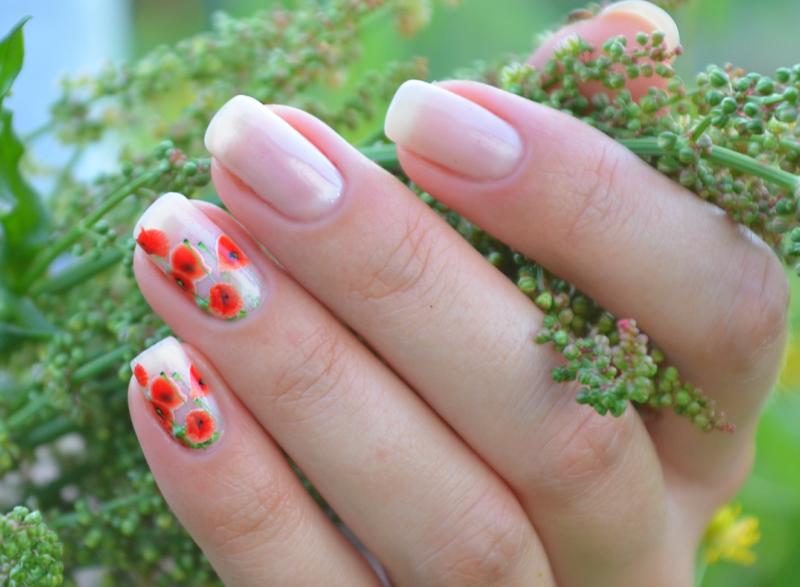 Naakte manicure met stickers in de vorm van papavers.