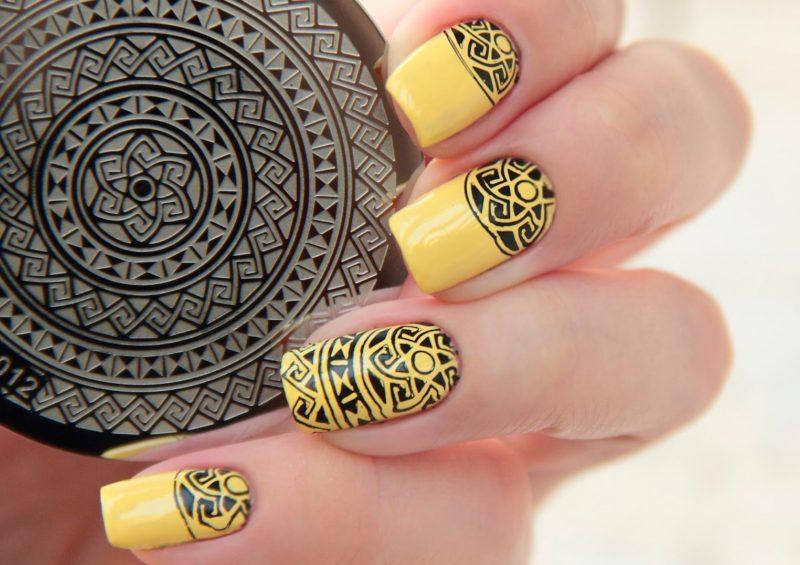Geltonas manikiūras su juodo etninio antspaudo modeliu.