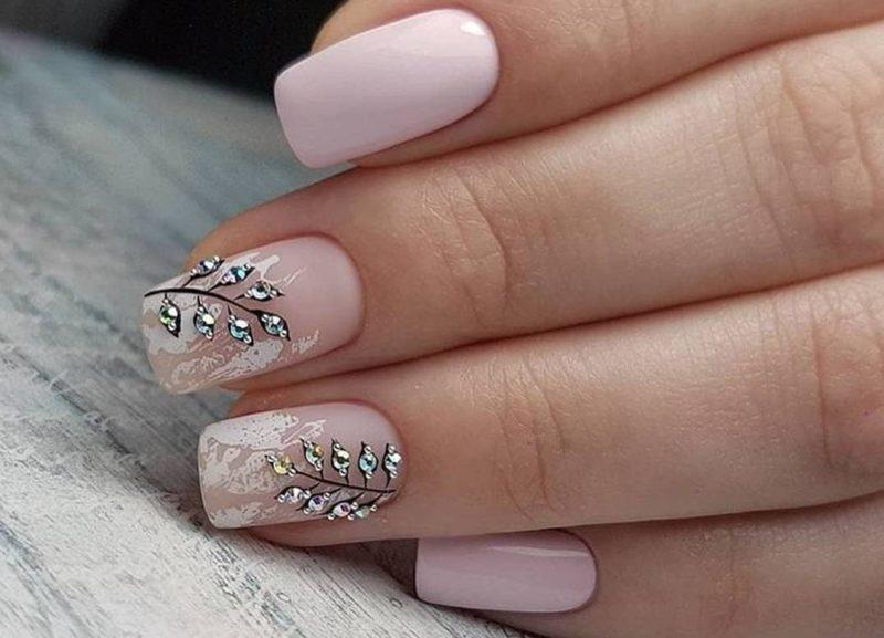 Roze manicure met bloemmotief en strass steentjes.