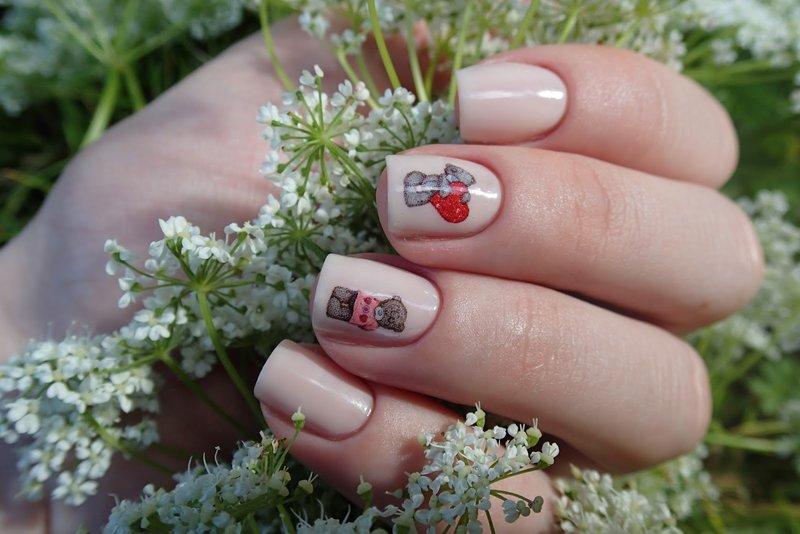 Zachte vleeskleurige manicure met stickers voor beren