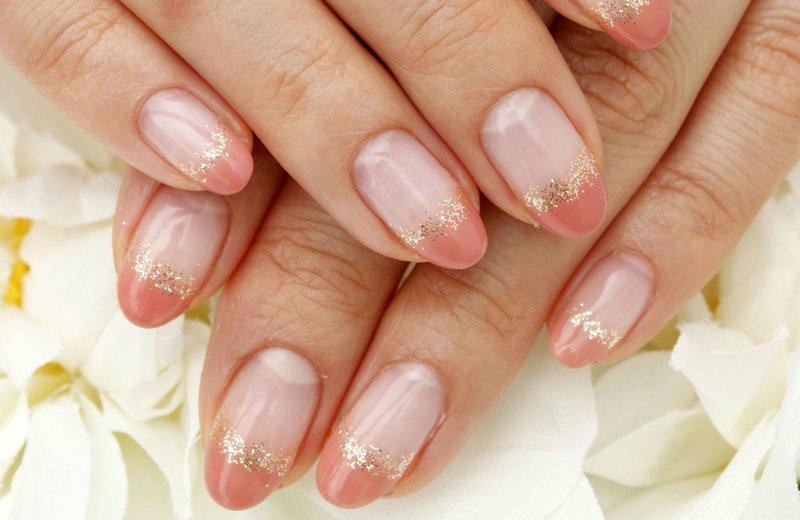 Naakte nagels met oranje jas en gouden pailletten