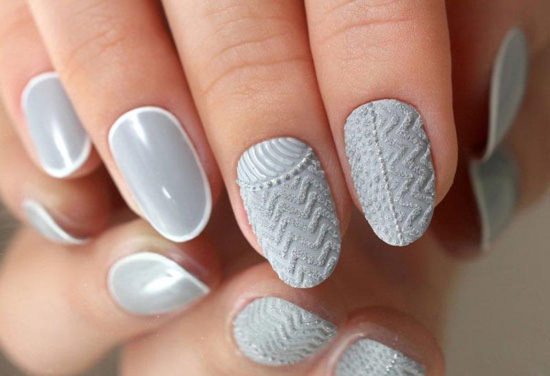 Manucure grise avec des motifs tricotés.