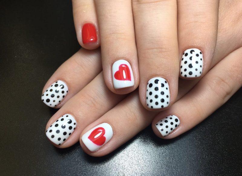Manucure blanche avec des points noirs et un coeur.