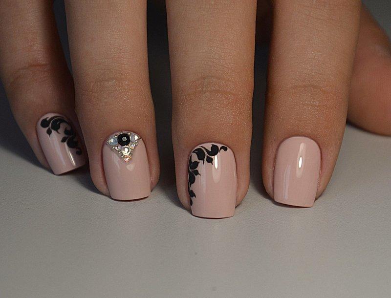 Naakte manicure met zwarte patronen en strass steentjes
