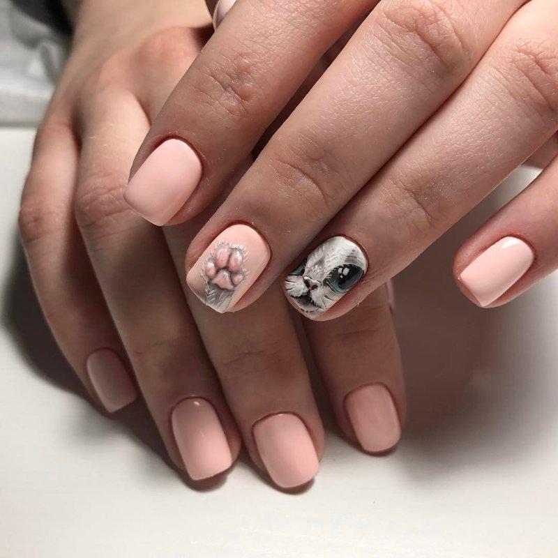 Roze en beige manicure met een kattenpatroon.