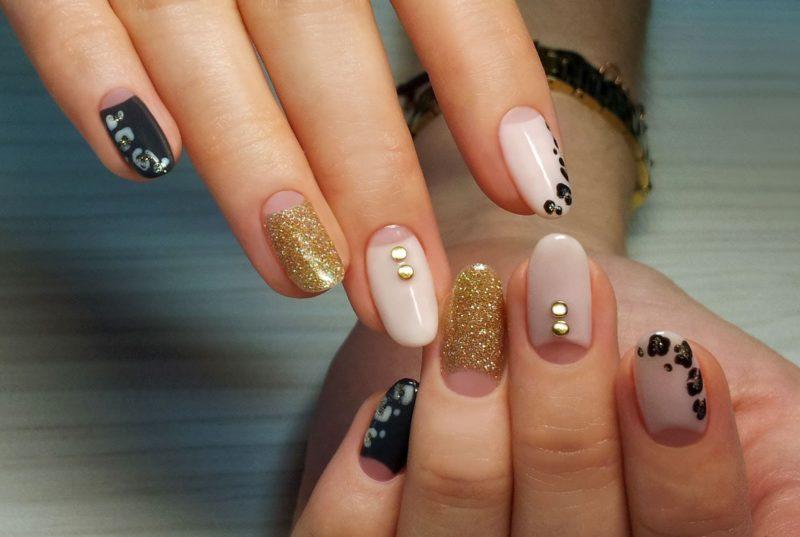 Gouden glitter naakt manicure met sieraden en luipaardprint.