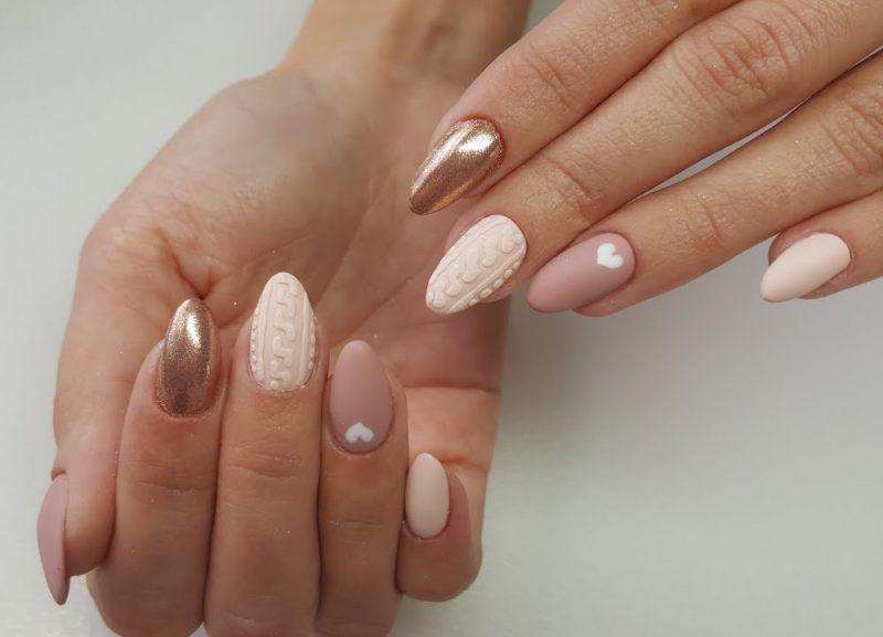 Naakte manicure met een matte afwerking, gouden glitter en volumetrisch patroon.