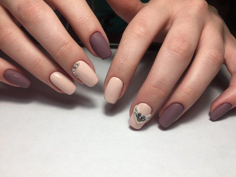 Naakte matte nagels met een hart van steentjes en bouillons