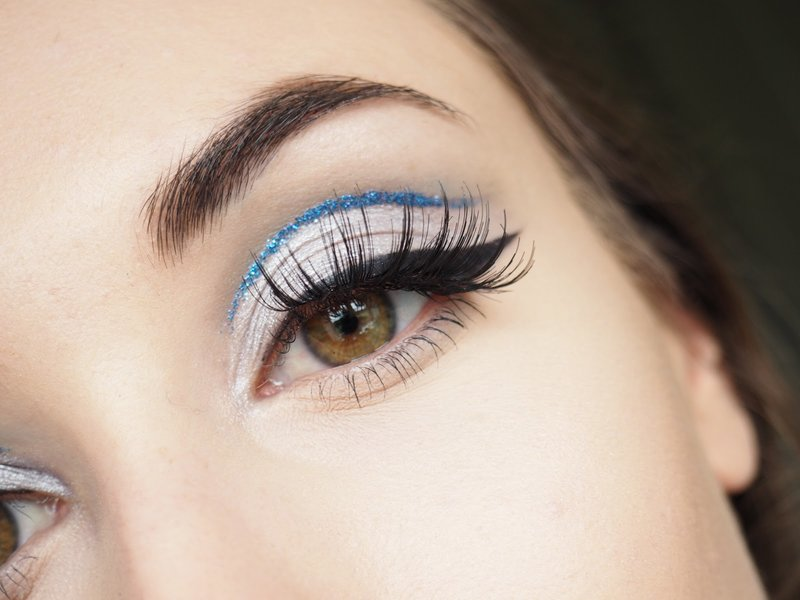 Minimalistinio kirpimo raukšlėtis su blizgiais mėlynais akių kontūro pieštukais