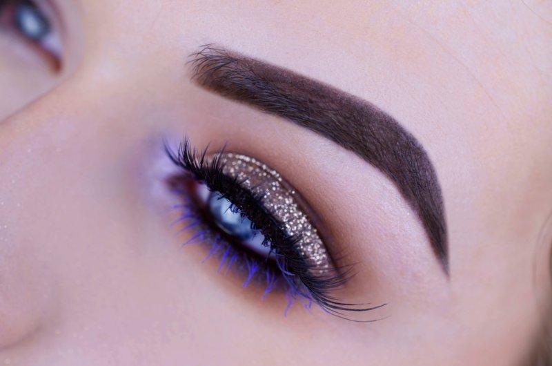 Auksinis makiažas su blizgučiais ir violetiniu tušu