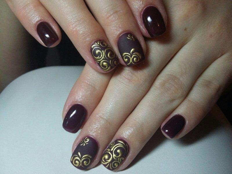 Bourgondische manicure met gouden monogrammen.