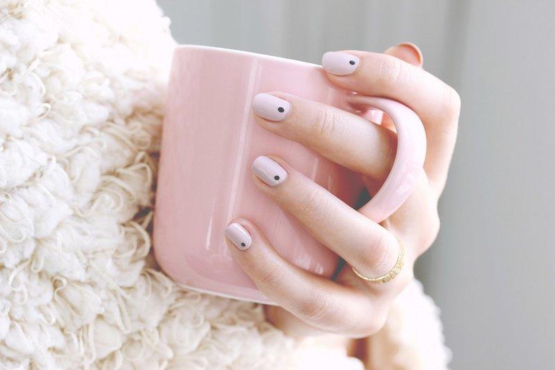 Minimalistische manicure met zwarte stippen.