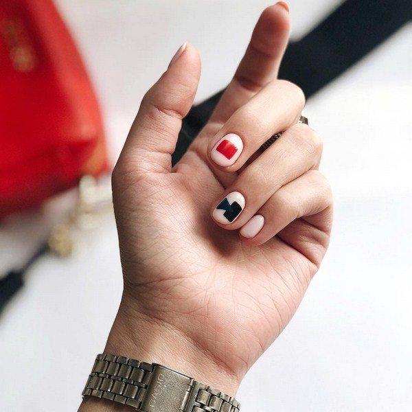 Geometrische manicure in zwarte en rode kleuren op basis van naakt.