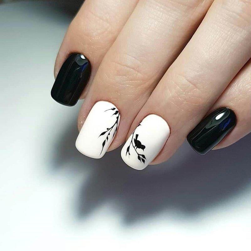 Stijlvolle zwart-witte manicure met een samenstelling van de lente