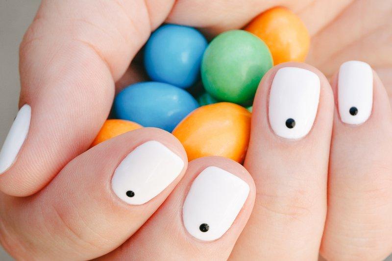 Zwarte stip manicure op een witte coating