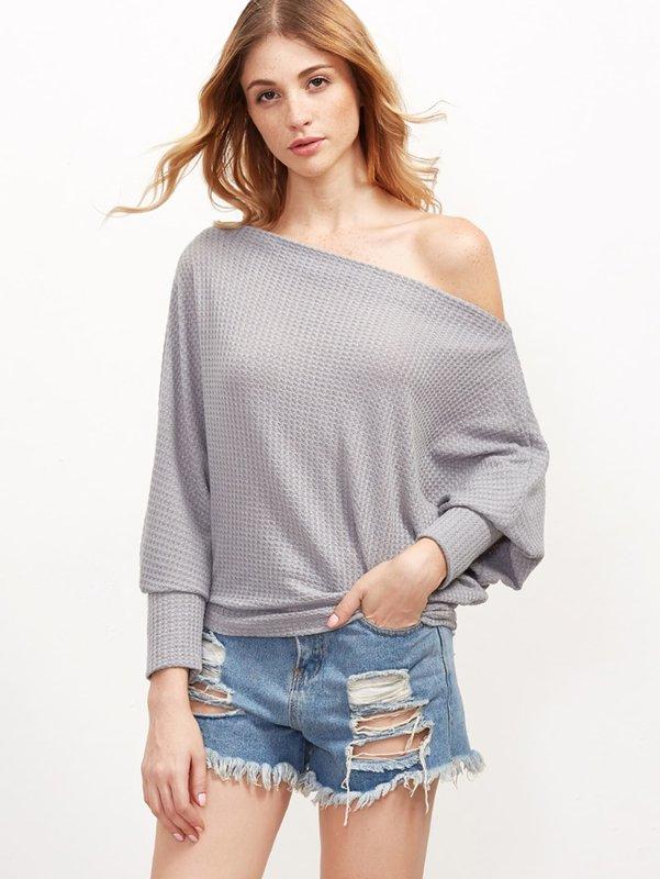 Meisje in een trui met blote schouders en korte shorts.