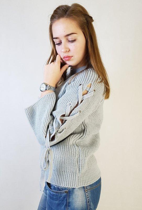 Meisje in een trui met stropdas langs de mouwen