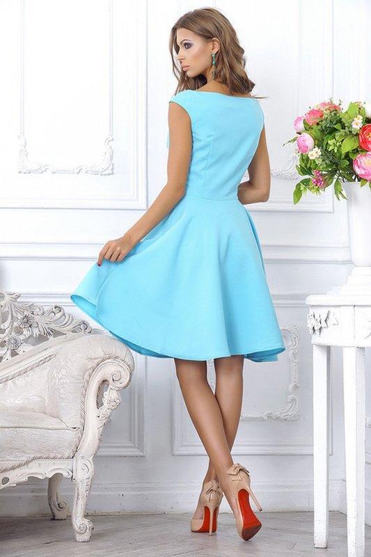 Meisje in een blauwe cocktailjurk met een boothals en een rok.