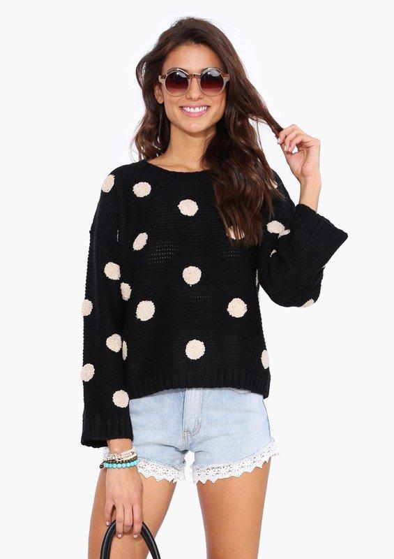 Meisje in een trui in grote erwten en shorts.