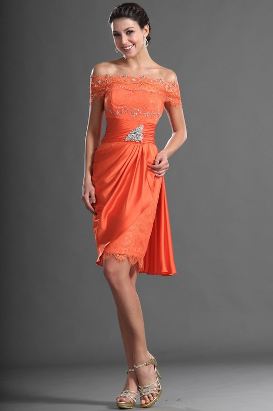 Meisje in een oranje cocktailjurk met blote schouders en strass steentjes
