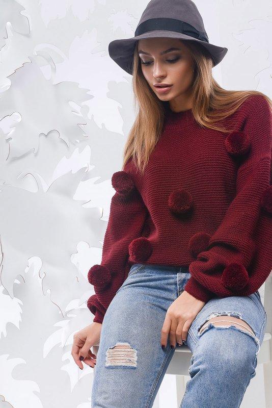 Meisje in een trui met effen pompons