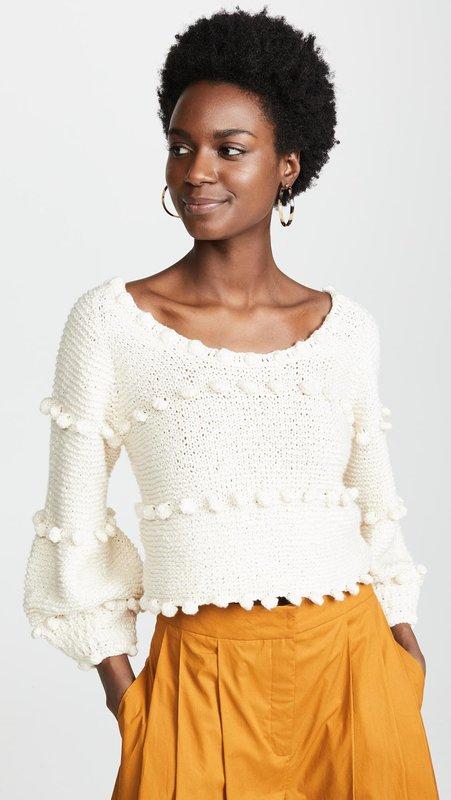 Meisje in een trui met pompons en een rok