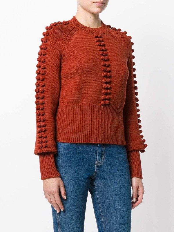 Meisje in een trui met getextureerde pompons