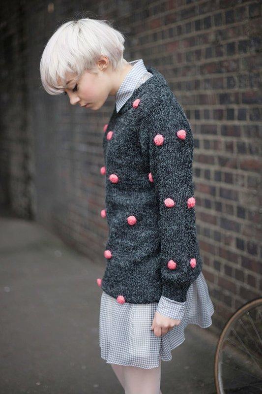 Meisje in een trui met roze pompons over een jurk