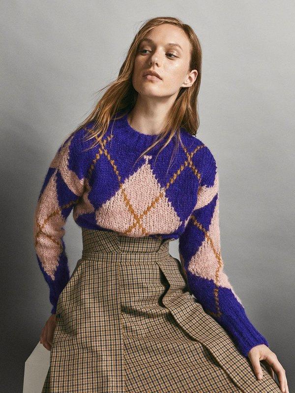 Meisje in een diamanten trui met een rok
