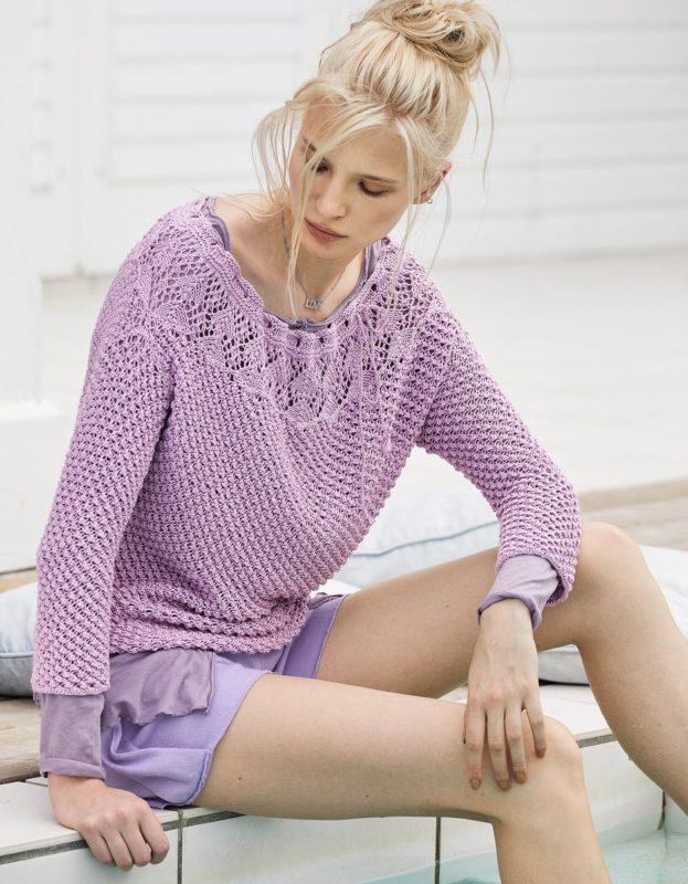 Meisje in een opengewerkte trui gekleed over een zomerjurk