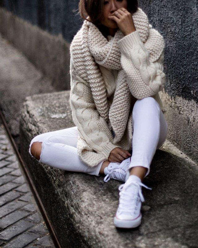 Meisje in een grote gebreide trui en een brede kraag