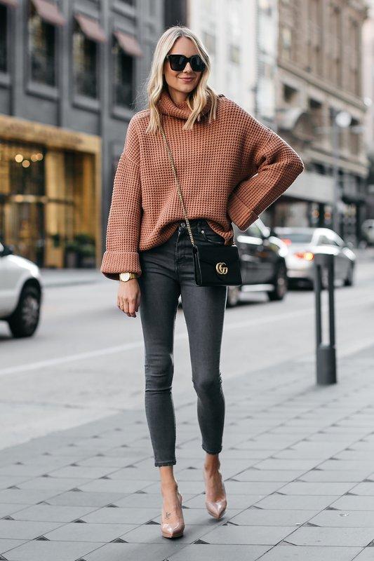 Meisje in oversized trui met jeans.