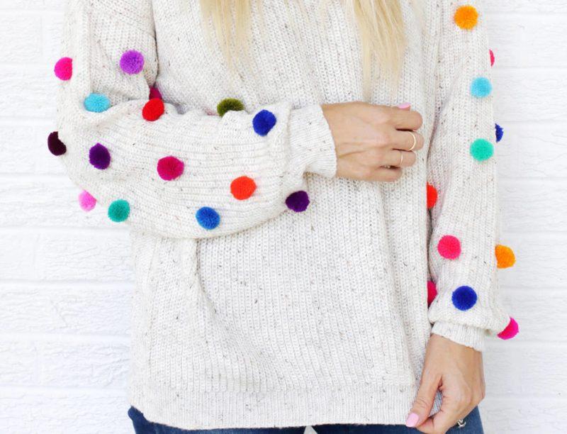 Meisje in een trui met pompons