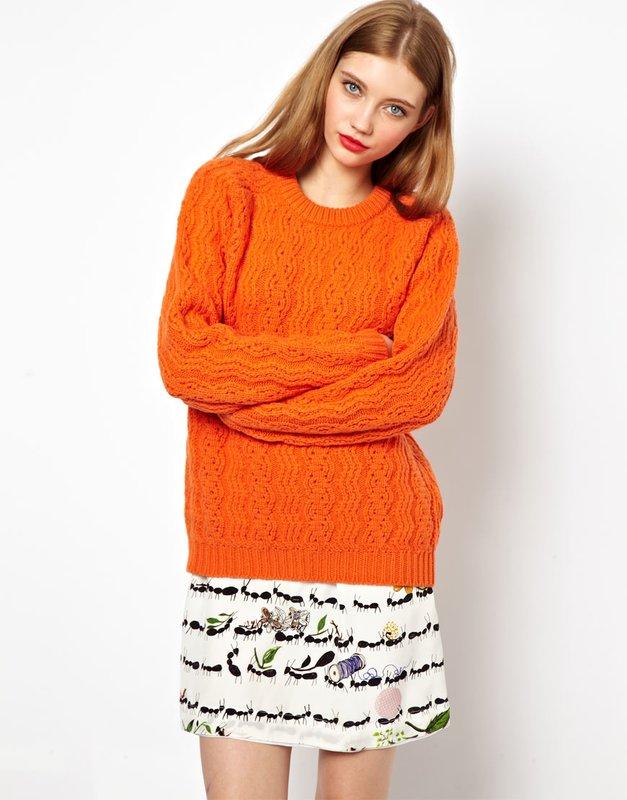 Meisje in een oranje trui en rok